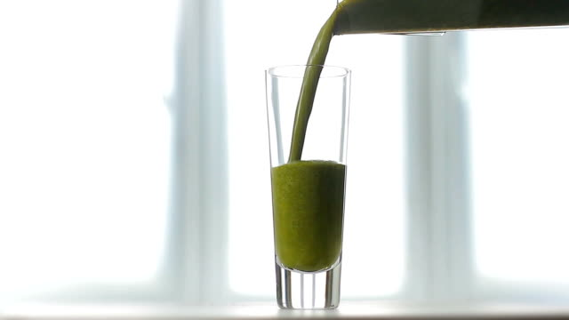 Celery fresh juice poured into glass. video