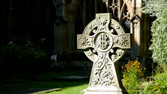 Celtic Christian cross in a churchyard. video