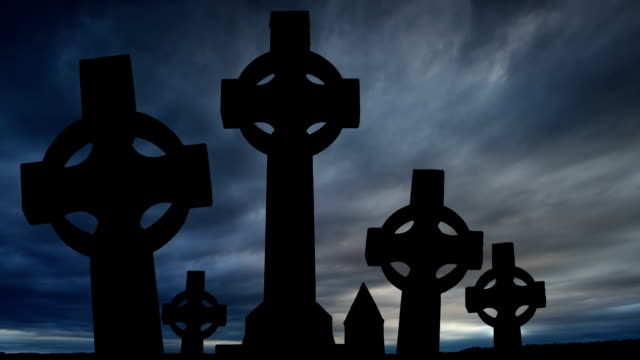 celtic crosses at dusk with dark clouds time lapse video
