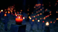 Cemetery at night with colorful candles for All Saints Day. All Saints' Day is a solemnity celebrated on 1 November by the Catholic Church. Static shot video
