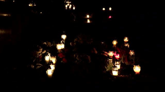 cemetery decorated with candles for All Saints Day at night. blur out. FullHD video