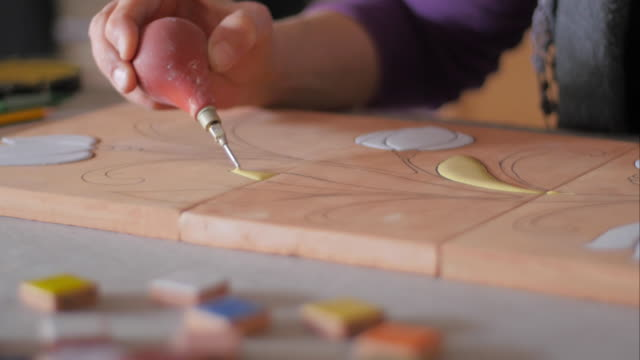 Ceramic maker filling pencil strokes on terracotta with rubber bulb in front of color samples video