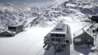 AERIAL Chairlift carrying skiers uphill on sunny winter day video