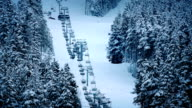 Chairlift Going Up Mountain Near Trees In The Snow video