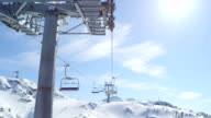 FPV: Chairlift ride in sunny mountain ski resort in snowy winter video
