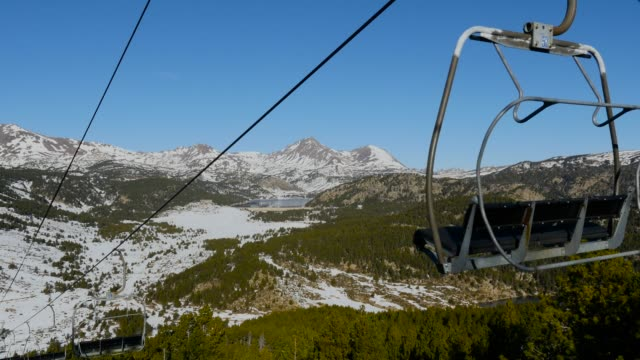 Chairlift with snowy mountains in the background. video
