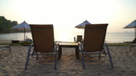Chairs and umbrella on tropical beach at sunset video