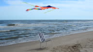 Chaise lounge on the beach, the sea and a kite. video