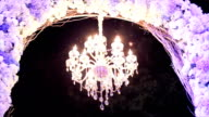 chandelier in the restaurant on wedding, the light in the room by a beautiful chandelier decoration and flower arch foreground. video