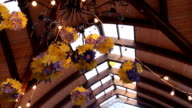 Chandelier is richly decorated with garlands made from artificial flowers video