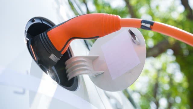 Charging electric car under green trees video