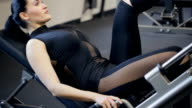 Charming brunette exercise press legs on traineger in gym video