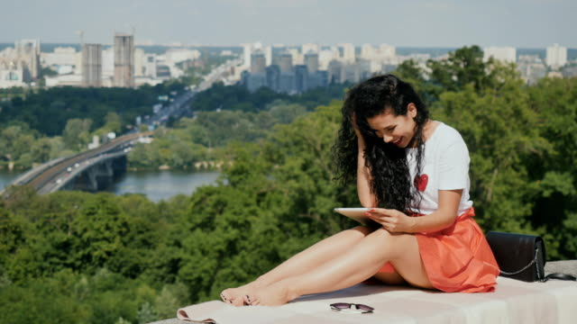 Charming brunette relax with tablet on city background video