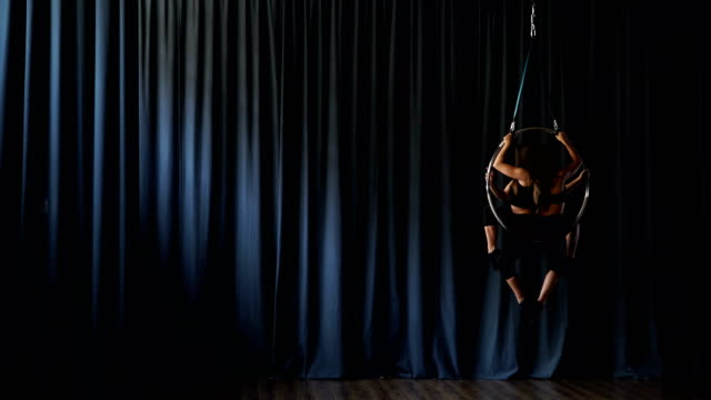 Charming gymnasts performs a trick in the aerial hoop video
