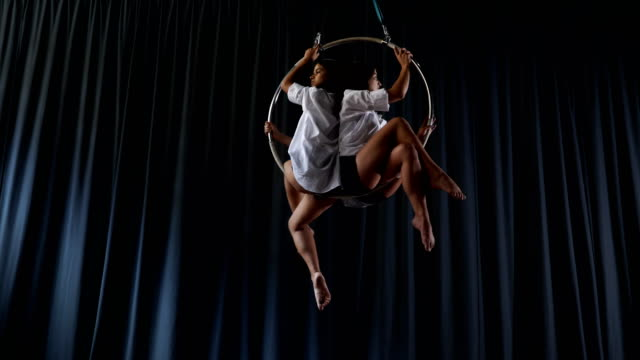 Charming gymnasts sits and spins in the aerial hoop video