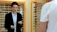 Charming optician selling glasses in optical shop video