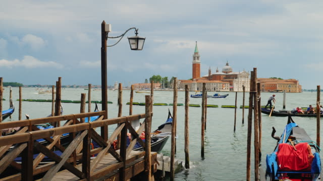 Charming Venice. Gulf with gondolas and intensive traffic of ships. Pier with wooden piles in the foreground video