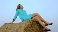 Charming woman sitting on a haystack on blue sky background. video