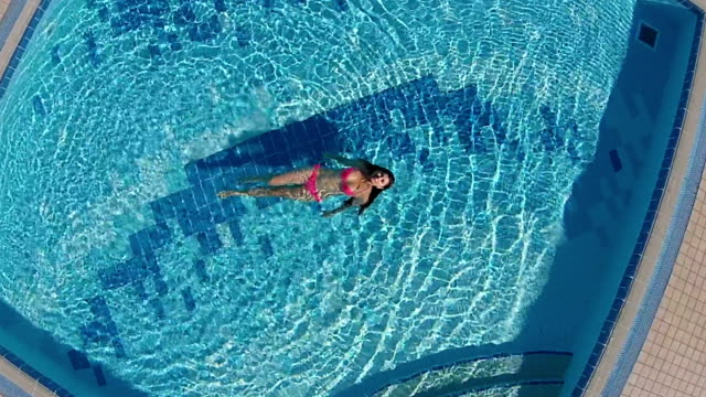 Charming woman swimming in the blue pool video