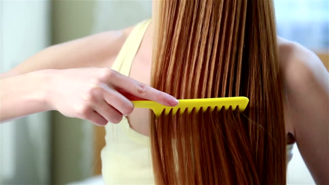 Charming young red-haired woman combing her hair long hair, sitting on the bed in the bedroom. video