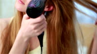 Charming young red-haired woman dries the hair dryer her long hair, sitting on the bed in the bedroom. video