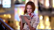 Charming young woman enjoying a tablet with a touch screen in the mall. video