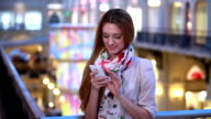Charming young woman uses a smartphone with a touch screen in the mall. video