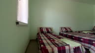 Cheap budget hotel room interior with three beds pan shot video