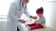 Check up on knee reflex with medical hammer on baby girl video