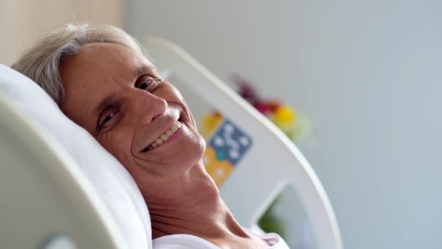 Cheerful aged man lying in a hospital bed video