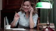 Cheerful and laughing woman talking on the phone resting after work video