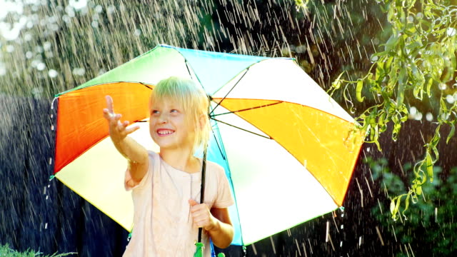 Cheerful blonde girl enjoys the rain five years. Hiding under a colorful umbrella video
