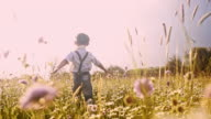 SLO MO Cheerful boy running through meadow with arms outstretched video