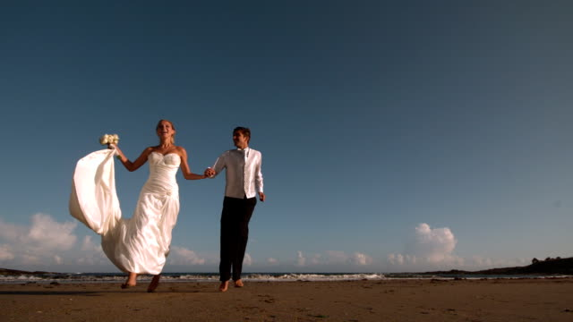 Cheerful bridal couple running on the beach video