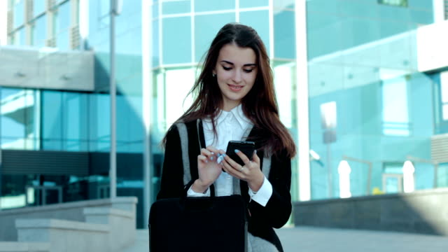 cheerful business girl working with mobile phone video