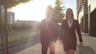SLOW MOTION: Cheerful businessman and businesswoman walking through business district video