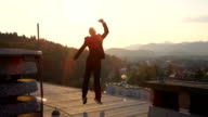 CLOSE UP: Cheerful businessman jumping with one hand raised on rooftop at sunset video