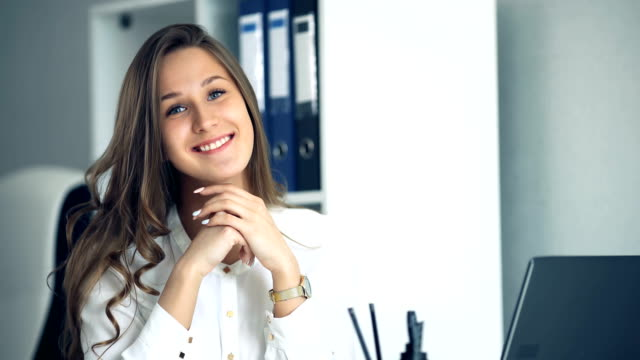 Cheerful businesswoman sitting at the table in office and looking at camera video