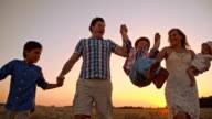 SLO MO Cheerful family relaxing in wheat field at sunset video