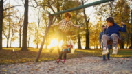 SLO MO Cheerful family swinging in the park video