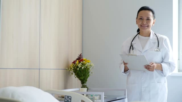 Cheerful female doctor standing in a hospital ward video