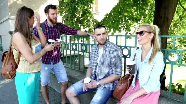 Cheerful friends in the street drinking coffee video