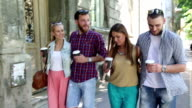 Cheerful friends walking in the street and drinking coffee video