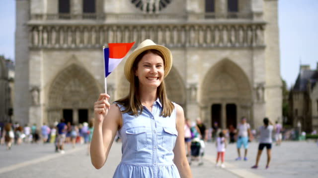 Cheerful girl enjoying vacation. Tourist in hat standing near Notre Dame of Paris. Waving French flag video