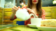 Cheerful girl having her dessert and green tea in a cafe video