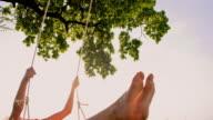 SLO MO Cheerful girl swinging on a tree swing video