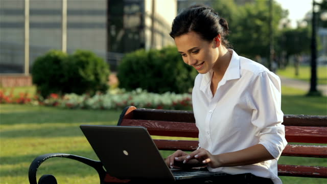 Cheerful girl with laptop on the bench video