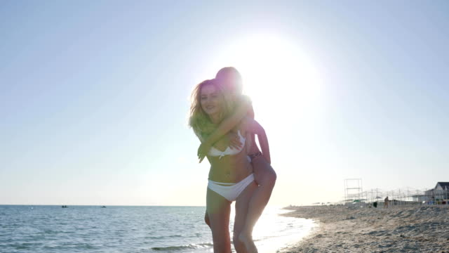 cheerful girlfriends laugh on shore of ocean, girls with sports video