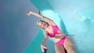 Cheerful happy blonde woman with pretty smile sliding down the waterslide toboggan having fun in summer aqua park video
