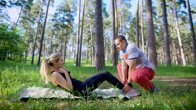 Cheerful husband and wife doing sports exercises in a park on the grass, a woman is rocking a press, a man helps her by holding her feet video